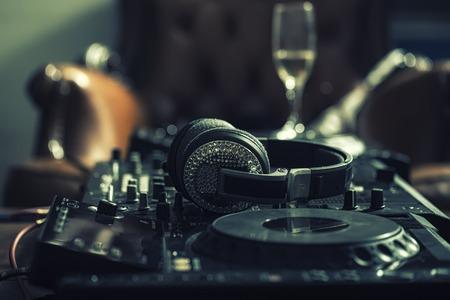 electronica musica: Dj mezclador musical profesional consola negro con muchos botones y perillas y auriculares glamour con pastas en el club de noche o estudio en el sofá de cuero marrón y el fondo de la copa de vino, cuadro horizontal Foto de archivo