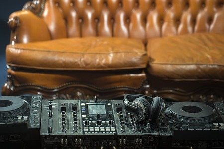 pastes: Front view of dj musical mixer professional black console with many buttons and knobs and glamour headphones with pastes in night club or studio on brown leather sofa background, horizontal picture Stock Photo