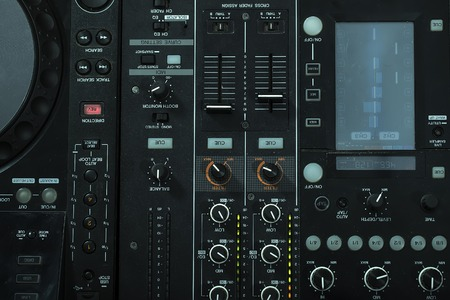 Upper view closeup of dj musical mixer electronic professional console black color with many buttons and knobs in night club or studio on digital background, horizontal picture Stock fotó