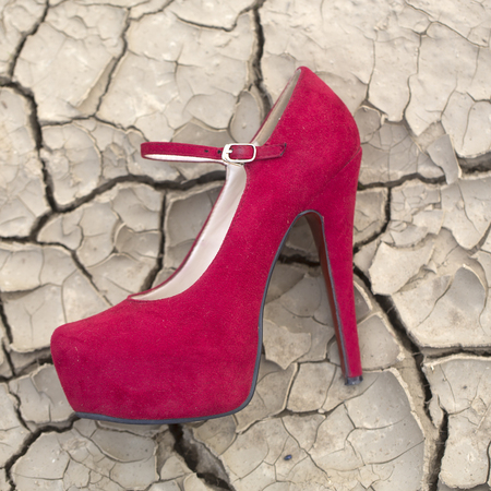 no heels: Textured desighn natural closeup background of cracked dry soil old grey ground in hot weather in droughty region with many splits and fissures with red suede high heeled shoe, horizontal picture