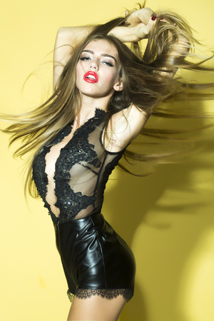 leather woman: Fashionable young beautiful woman with long lush hair and red lips in stylish short black overalls from lace and leather standing with raised hands in studio on yellow background, vertical picture Stock Photo