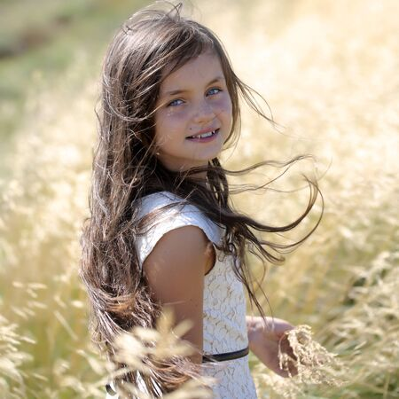 white day: Portrait of pretty young brunette smiling girl with long hair in white lace dress looking forward standing in valley among yellow spikelet sunny windy day outdoor, square photo Stock Photo