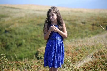 spaciousness: Small pretty brunette girl in blue lace summer dress looking away standing in mountain valley with deep dry spikelet grass sunny windy day outdoor on natural background, horizontal picture