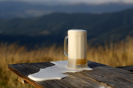 porter: One glass mug with lager or porter tasty frothy beer on wooden table top sunny day outdoor on natural with mountain hills and yellow dry grass background, horizontal picture