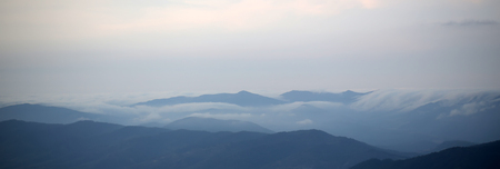 spaciousness: Beautiful spaciousness panoramic landscape view from high hill top on many mountain humps with deep green forests and cloudy grey blue sky on natural background, horizontal picture