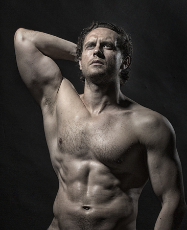 bare breast: Handsome strong sullen naked muscular unshaven male bodybuilder with beautiful straight athletic body standing with raised hand and bare chest looking away on studio black background, vertical photo Stock Photo