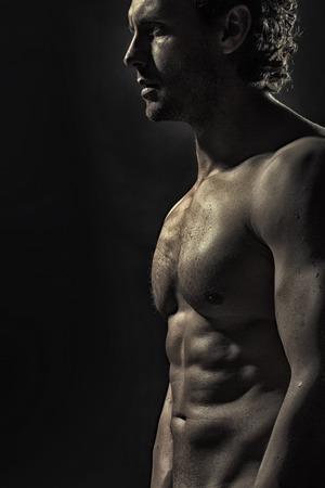 m�nner nackt: Eine attraktive starke junge nackte Schwei� muskul�ses m�nnliches Baumuster mit dem lockigen Haar und sch�nen geraden K�rper, die im Studio auf schwarzem Hintergrund, vertikale Bild,