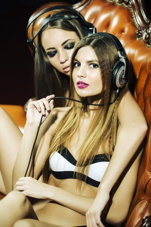 Two pretty young glamour dj women with bright make-up and long hair in underwear and headphones sitting on brown leather royal chair in night club indoor closeup, vertical picture