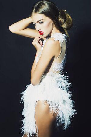 pluma: Moda hermosa mujer sensual posando con el pelo enorme largo vestido blanco corto de c�ctel elegante con encaje y plumas de pie con las manos levantadas en el estudio sobre fondo negro, imagen vertical Foto de archivo