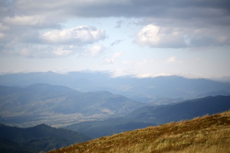 spaciousness: Beautiful spaciousness landscape view from high hill top on many mountain humps with deep green forests and cloudy grey blue sky on sunny natural background, horizontal picture Stock Photo