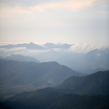 spaciousness: Beautiful spaciousness landscape view from high hill top on many mountain humps with deep green forests and cloudy grey blue sky on natural background, square picture Stock Photo