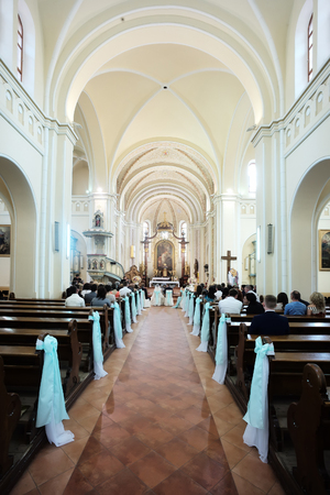 sanctified: Beautiful white bows decorated aisle for wedding bride and groom in bright arched hall of Catholic Church, vertical photo