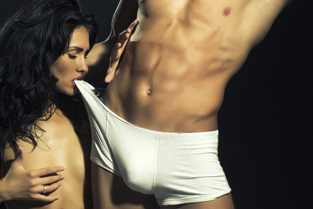 Sexy young naked couple of muscular boy in white underwear and girl undressing man with teeth touching chest standing in studio on black background, horizontal photo
