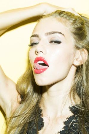 labios rojos: Retrato de moda modelo de la hembra bonita que lame los labios rojos con la lengua en la ropa negra elegante de encaje de pie con la mano levantada mirando hacia adelante en el estudio de fondo close-up, imagen vertical