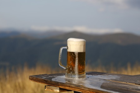 mug of ale: One glass mug with lager or porter tasty frothy beer on wooden table top sunny day outdoor on natural with mountain hills and yellow dry grass background, horizontal picture