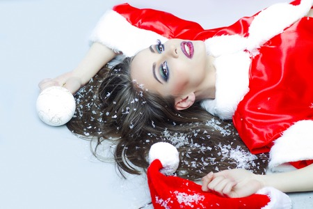 winter fashion: One beautiful sexual young smiling brunette woman in red coat of santa with white fur and decorative new year tree ball holding in hands lying in studio on light background, horizontal picture