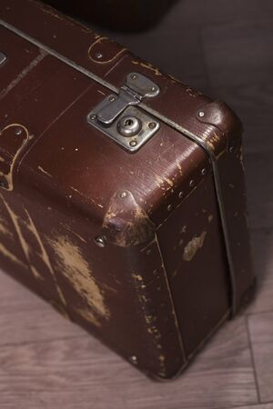 brown leather: Closeup of old fashioned aged brown leather brief case standing indoor in studio, vertical picture