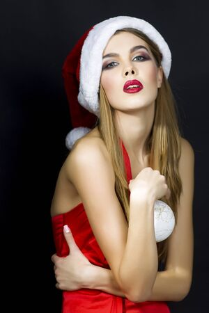 black hat: One beautiful sexual young blonde woman in red dress hat of santa with white fur and decorative new year tree ball holding in hands standing in studio on black background, vertical picture