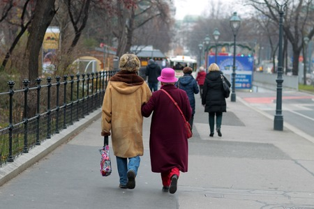 cold woman: Two elderly ladies are strolling around the city on cold winter day wearing stylish clothes and holding each other under hand Stock Photo