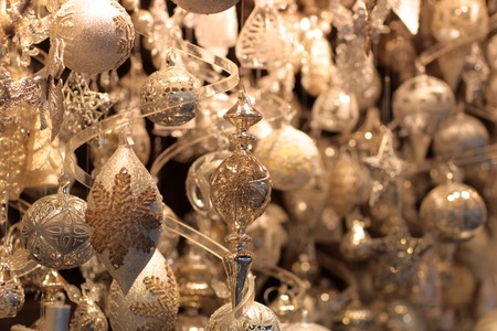 glitzy: Many glittery tree toys with different ornaments are hanging under ceiling with blured background creating Christmas mood
