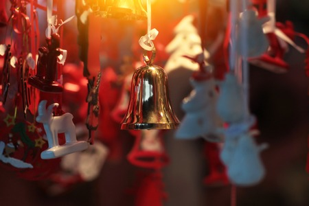 glitzy: Gold Christmas bell is hanging among many red and white tree toys with blured background creating holiday mood