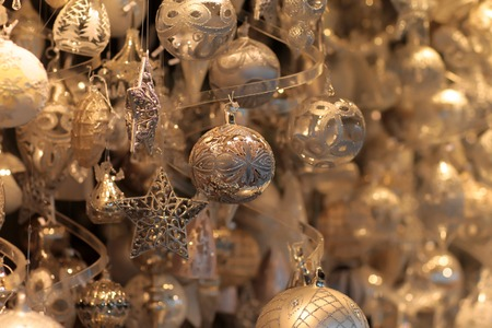 sparkly: Many sparkly tree toys with traditional ornaments are hanging under ceiling with blured background creating Christmas mood