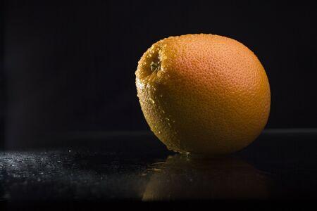 amarillo y negro: One ripe tasty beautiful seasoning citrus fruit of wet orange with water spray lying in studio on black background, horizontal picture