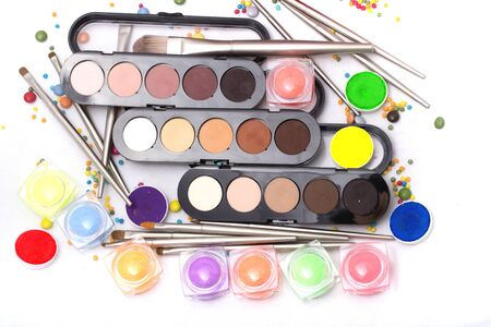 eyemakeup: Set of many professional visagiste eyeshadow palette red orange green violet pink yellow purple black beige brown colors foundation powder and make-up brushes on white background, horizontal picture