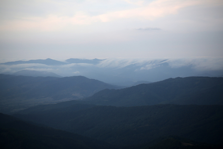 spaciousness: Beautiful spaciousness landscape view from high hill top on many mountain humps with deep green forests and cloudy grey blue sky on natural background, horizontal picture Stock Photo
