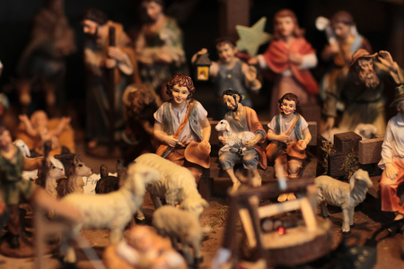 good shepherd: Scene where three shepherds are sitting on the bench holding one sheep and smiling because of Jesus birth and other figures of people and sheep are blurred