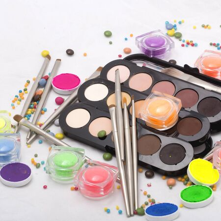 gold facial: Set of many professional visagiste eyeshadow palette red orange green violet pink yellow purple black beige brown colors foundation powder and make-up brushes on white background, horizontal picture
