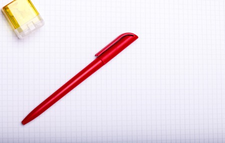 one sheet: One plastic pen red color and yellow sharpener lying on white paper sheet on school background copyspace, horizontal picture