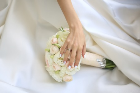 pion: Beautiful fresh soft wedding decorative bouquet of white peony and rose flowers lying on dress of bride with female hand closeup, horizontal picture Stock Photo