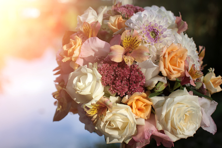 alstromeria: Closeup of beautiful fresh colorful wedding decorative bouquet of rose alstromeria and chrysanthemum outdoor on blurred water natural background in sunlight, horizontal picture Stock Photo