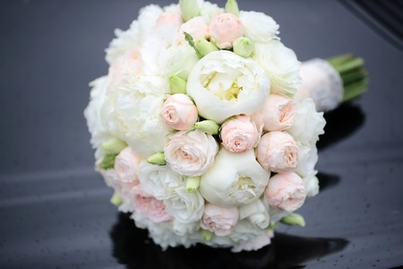 Beautiful fresh soft wedding decorative round shape bouquet of pink rose white peony and green flowers lying on black glossy background outdoor, horizontal picture Foto de archivo