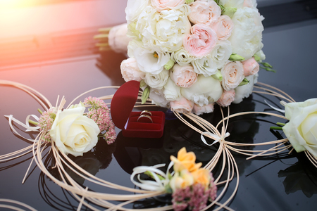 posy: Red velvet box with two wedding golden rings standing on black glossy background with decorative straw and colorful fresh posy of rose and other flowers, horizontal picture