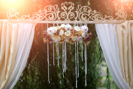 Closeup of beautiful fresh colorful wedding decorative arrangment of rose alstromeria and chrysanthemum with crystal beads on arch outdoor on blurred natural background in sunlight, horizontal picture