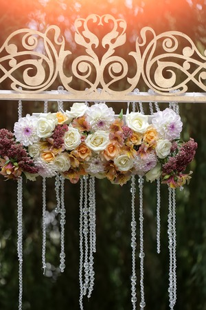 alstromeria: Closeup of beautiful fresh colorful wedding decorative arrangment of rose alstromeria and chrysanthemum with crystal beads on arch outdoor on blurred natural background in sunlight, vertical picture