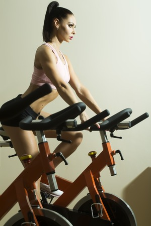 stationary bike: Beautiful white woman with dark hair bright makeup and athletic figure in black shorts and pink top do exercise on stationary bike in gym, vertical photo