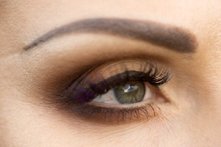 eyebrow: Closeup photo of beautiful female eye with grey pupil which reflects sky and evening makeup of brown eyeshadow black eyeliner mascara with violet tint and neat eyebrow, horizontal picture Stock Photo