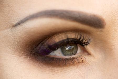 Foto van mooie vrouwelijke oog met grijze pupil close-up, die hemel en 's avonds make-up van bruine oogschaduw zwarte eyeliner mascara met paarse tint en netjes wenkbrauw, horizontaal beeld weerspiegelt