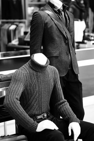 mannequin: Couple of male fashion mannequins dressed in casual style sitting and standing over dark grey selling floor background black and white, vertical picture