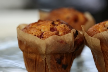 muffin: Closeup of some homemade sweet delicious chip berry muffins in muffin case on white background, horizontal picture Stock Photo