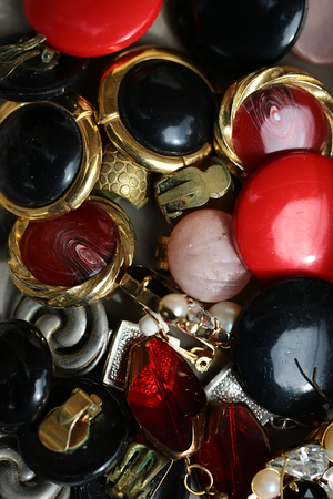 dozens: Variety dozens different colour golden silver old-fashioned time-worn used vintage bijouterie collection of imitation jewellery frosted transparent glazy dum earclips piled together, vertical picture