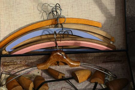 Closeup boot trees and varnish retro wooden coat hanger against lots of vintage clothing hangers angular frames made of timber  painted coloured tired aged background, horizontal picture