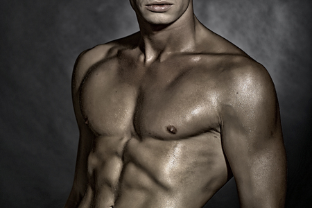 männer nackt: Nahaufnahme von einem jungen sexuellen nackte Mann mit schönen nassen muskulösen starken Körper und Oberkörper stehend im Studio auf grauem Wandhintergrund, horizontale Abbildung