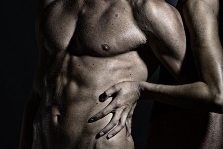 hot breast: Крупным планом небеленой сексуальной человека с красивой мокрой мышечный орган и женских руках, касаясь мужской шесть пакет стоя в студии, горизонтальный изображение