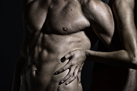 sex tenderness: Closeup of undressed sexual man with beautiful wet muscular body and female hands touching male six-pack standing in studio, horizontal picture