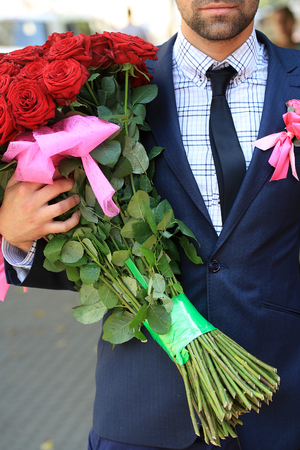 birthday suit: Man in blue suit with jacket holding one big beautiful colorful soft aroma fresh wedding or birthday bouquet of many red rose flowers outdoor on natural background, vertical picture Stock Photo
