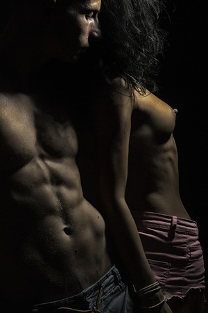 man and woman sex: Half dressed sexual passionate pair of two people man with beautiful muscular body touching young woman with bare breast standing in studio close to each other on black background, vertical picture